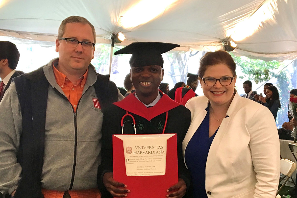 Josh posing with his friends David and Megan. Josh is wearing a cap and gown and holding a Harvard document.