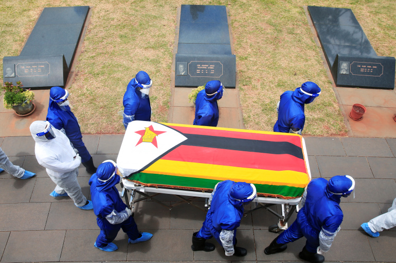 Pallbearers in Harare carry a coffin at the burial of two cabinet ministers and a retired general who died after contracting COVID-19 [Philimon Bulawayo/Reuters]