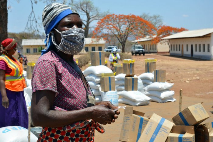 Loveness waits to pick up a month's worth of food assistance. © WFP/Adrienne Bolen