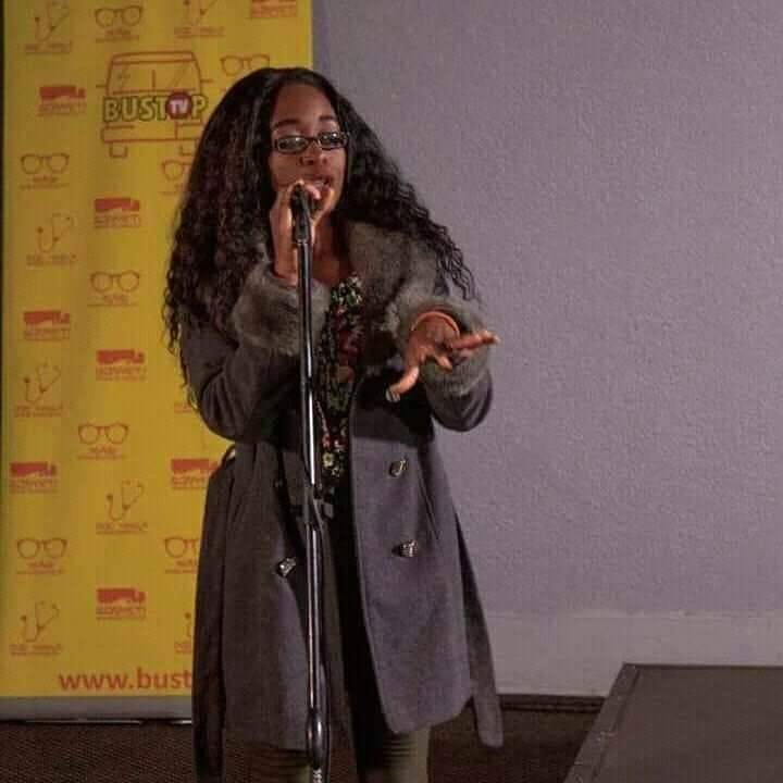 Against a yellow backdrop, a woman with long hair and wearing agree coat holds a microphone, her other hand held up with fingers splayed.
