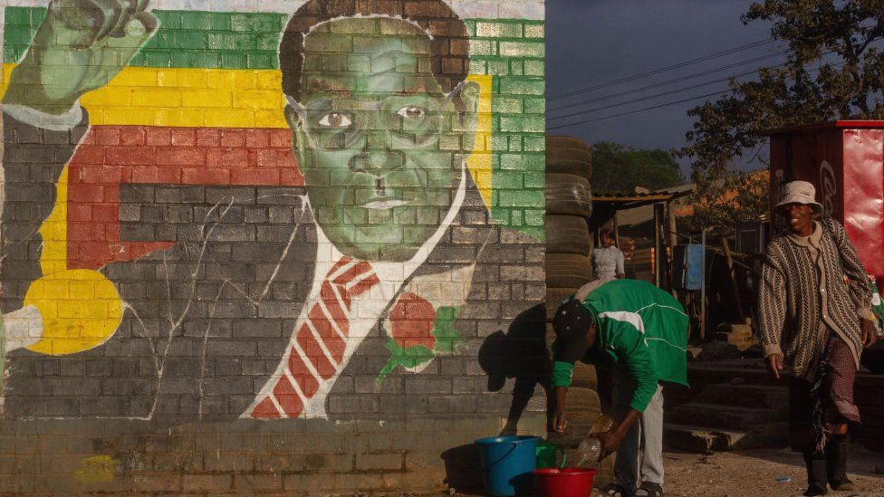 People in Mbare, Harare, by a mural of Zimbabwe's late President Robert Mugabe - 2019