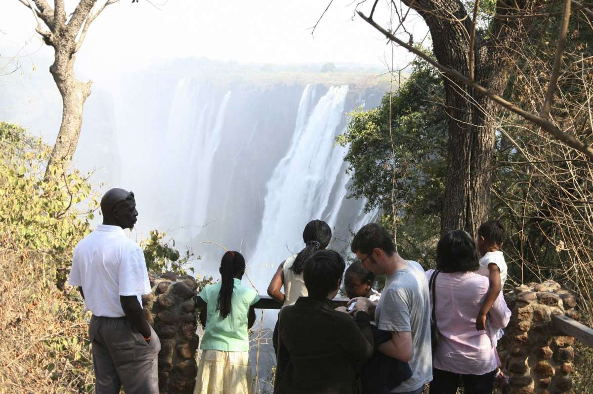 FILE - In this Sept. 23, 2007 file photo, people watch the Victoria Falls in Zimbabwe. Zimbabwe's Victoria Falls usually teems with tourists who come to marvel at the roaring Zambezi River as it tumbles to the gorge below and sends up a mist that is visible from miles away. The waterfall is still mighty, but the COVID-19 pandemic has reduced visitors to a trickle. To promote Victoria Falls as a safe destination, the Zimbabwean government made vaccines available to all 35,000 residents of the town that shares a name with the waterfall.