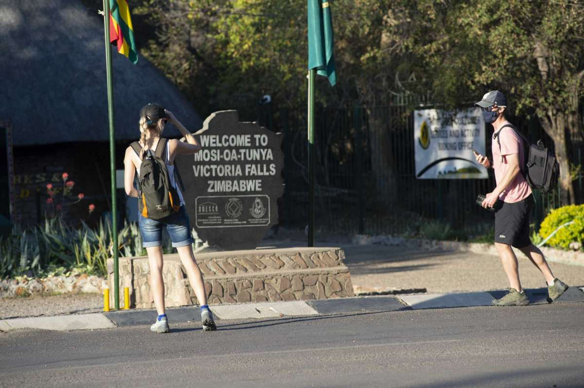 Tourists wear face masks at the entrance of the Victoria Falls in Victoria Falls in this Friday, Aug, 6, 2021 photo. To promote Victoria Falls as a safe tourist destination, President Emmerson Mnangagwa's government has made vaccinations available to all 35,000 residents of the town, and an estimated 60% of the people in Victoria Falls have now been vaccinated with either the Sinopharm or Sinovac vaccines, both from China.